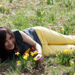 Woman lying in grass with daffodils — Stock Photo