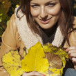Fall woman holding autumn leaves — Stock Photo #13879463