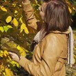 Pretty woman among autumn leaves — Stock Photo