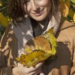 Woman playing with autumn leaves — Stock Photo