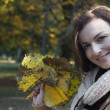 Beautiful woman with fall leaves — Stock Photo