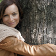 Pretty young woman hugging tree in a park — Stockfoto