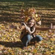 Woman drop leaves in autumn park — Foto de Stock