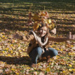 Woman drop leaves in autumn park — ストック写真