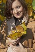Mulher brincando com folhas de outono — Fotografia Stock