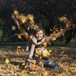 Woman throwing leaves in fall — Stockfoto