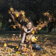 Woman throwing leaves in fall - Stock Photo