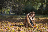 Attractive young woman and fall leaves — Стоковое фото