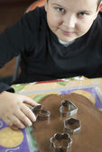 Little boy cutting dough for christmas cookies — Stock Photo