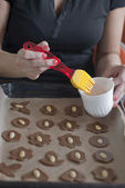 Glazing christmas cookies before backing with egg — Stock Photo