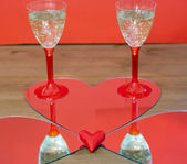 Mirroring of two champagne glasses and little heart — Stock Photo