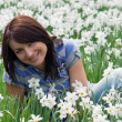 Smiling woman sitting among daffodils — Stock Photo