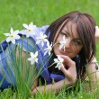 Young woman smelling daffodils — Stock Photo