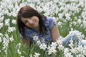 Young woman sitting among daffodils — Stock Photo