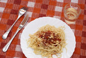 Spaghetti with sauce and glass of wine — Stock Photo