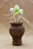 Ornamental easter eggs in a clay vase — Stock Photo