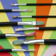 Foto Stock: Paint brushes and colored paper