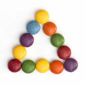 Colorful smarties in a triangle — Stock Photo
