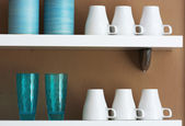 Mugs and cups stored on the shelf — Stock Photo