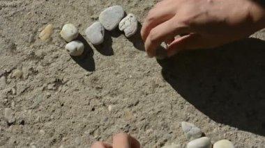 Human hands makes little heart of stones — Stock Video