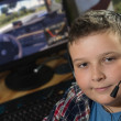 Boy with headphones is playing a computer game — Stock Photo