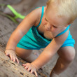 Stock Photo: Little blond girl climbs on ground