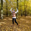 Stock Photo: Joyful caucasian woman jumping in the autumn leaves