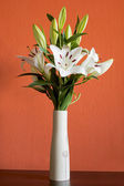Blooming white lilies in a slim vase — Stock Photo