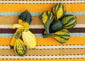 Ornamental gourds on the striped tablecloth — Stock Photo