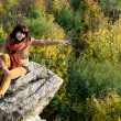 Young woman sitting on the rock and showing the autumn forest — Stock Photo #33872597