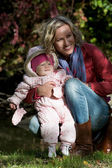 Young woman with little girl in autumn outdoors — Stock Photo