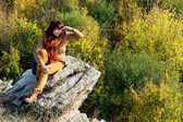 Young woman is sitting on the rock and watching to the autumn fo — Stock Photo