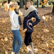 Two attractive young women posing with falling leaves — Stok fotoğraf