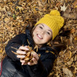 Beautiful smiling teenage girl lying in the autumn leaves — Stock Photo