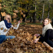 Two beautiful young women throwing yellow leaves — Stok fotoğraf