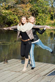 Two attractive women posing by the pond in the autumn park — Stock Photo