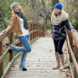 Two attractive young women laughing on a wooden bridge — ストック写真