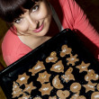 Beautiful young woman holding baking tray with gingerbread cooki — Stock Photo #35176831