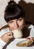 Beautiful brunette drinking coffee — Stock Photo