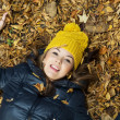 Young smiling teenage girl lying in the autumn leaves — Stock Photo