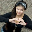 Young girl sending love heart — Stock Photo