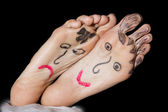 Painted faces on the woman's feet — Stock Photo