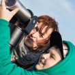Stock Photo: Young boy with her grandmother looking through telescope