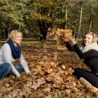 Two young caucasian women throwing yellow leaves — Stok fotoğraf