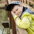 Young boy in baseball cap standing on the bridge and smiling — Stock Photo