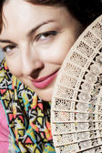 Beautiful smiling woman with a fan — Stock Photo