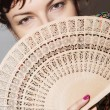 Young woman partly hidden behind a fan — Stock Photo #38890935