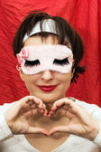 Attractive woman in sleep mask making heart shape with her hands — Stock Photo