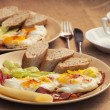 Two portions of ham and eggs with bread, radish, cheese and papr — Stock Photo