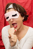 Attractive woman in sleeping mask imitates singing into a microp — Stock Photo
